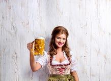 拿着啤酒的传统巴法力亚礼服的妇女 免版税库存图片