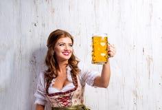 拿着啤酒的传统巴法力亚礼服的妇女 库存照片
