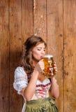 拿着啤酒的传统巴法力亚礼服的妇女 图库摄影