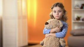 拿着喜爱的玩具熊的被抛弃的生气卷曲女孩感到哀伤在孤儿院 免版税库存照片