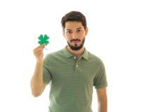 拿着四片叶子三叶草的英俊的人 免版税库存照片