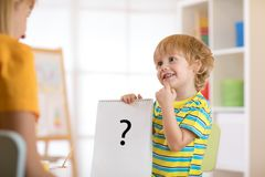 拿着图画的年轻男孩在疗法或教训期间与妇女 库存照片