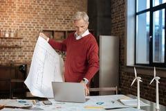 拿着图纸和键入在膝上型计算机的灰发的人 免版税库存图片