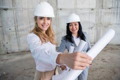 拿着图纸的可爱的微笑的建筑师,当工作在建造场所时 免版税库存照片