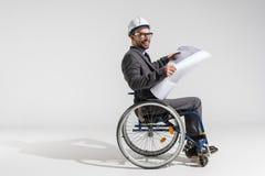 拿着图纸的轮椅的微笑的失去能力的建筑师 免版税库存照片