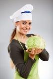 拿着圆白菜的妇女厨师 免版税库存照片