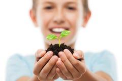 拿着土壤生长绿色新芽叶子的英俊的微笑的儿童男孩 免版税库存图片