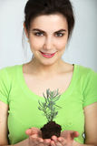 拿着土壤的美丽的妇女年幼植物 免版税库存照片