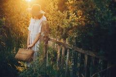 拿着土气秸杆篮子的亚麻制礼服的时髦的女孩在日落光的木篱芭 放松和摆在夏天的Boho妇女 免版税库存照片