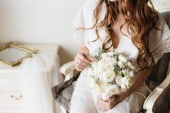 拿着土气花束的一件白色闺房礼服的新娘 新娘闺房 图库摄影