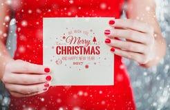 拿着圣诞快乐的卡片或信件的女性手对圣诞老人 免版税库存图片