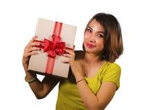 拿着圣诞礼物或有红色丝带的年轻愉快和美丽的亚裔印度尼西亚妇女画象生日礼物箱子 免版税库存照片