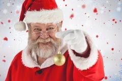 拿着圣诞节中看不中用的物品的快乐的圣诞老人画象的综合图象 图库摄影