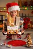 拿着圣诞节曲奇饼房子的少年女孩 免版税库存图片