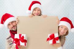 拿着圣诞节横幅的家庭 免版税库存照片