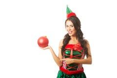 拿着圣诞节泡影和指向对此的妇女 库存图片