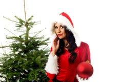 拿着圣诞节泡影的圣诞老人衣裳的妇女 免版税库存图片