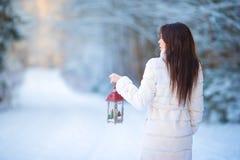 拿着圣诞节灯笼的少妇户外在美好的冬天雪天 免版税库存图片