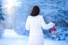 拿着圣诞节灯笼的少妇户外在美好的冬天雪天 免版税库存照片
