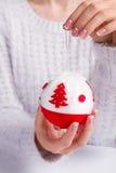 拿着圣诞节球的一件美丽的蓬松毛线衣的女孩 库存图片