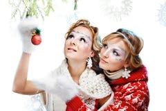 拿着圣诞节球的二个女孩 图库摄影