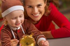 拿着圣诞节球的微笑的母亲和婴孩 库存图片