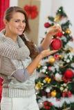 拿着圣诞节球的愉快的少妇 免版税库存照片