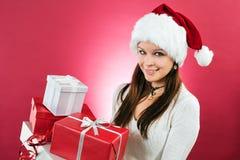 拿着圣诞节礼品的愉快的女孩 免版税库存照片