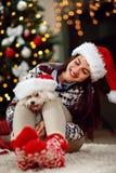 拿着圣诞节礼物小狗的女孩 免版税库存照片