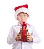 拿着圣诞节礼物想知道的wat的愉快的男孩 免版税库存图片