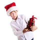 拿着圣诞节礼物想知道的wat的愉快的男孩 库存照片