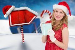 拿着圣诞节礼物的圣诞老人帽子的美丽的妇女 库存图片