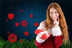 拿着圣诞节礼物的圣诞老人服装的美丽的妇女 免版税库存图片