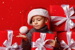 拿着圣诞节礼物的圣诞老人红色帽子的微笑的滑稽的孩子手中 圣诞节概念 免版税库存照片