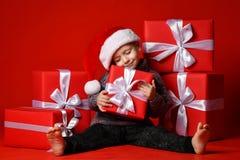 拿着圣诞节礼物的圣诞老人红色帽子的微笑的滑稽的孩子手中 圣诞节概念 库存图片