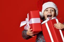 拿着圣诞节礼物的圣诞老人红色帽子的滑稽的微笑的孩子手中 免版税库存图片