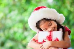 拿着圣诞节礼物的圣诞老人红色帽子的逗人喜爱的亚裔儿童女孩 免版税库存图片