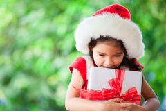 拿着圣诞节礼物的圣诞老人红色帽子的逗人喜爱的亚裔儿童女孩 免版税库存照片