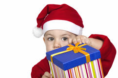 拿着圣诞节礼物的圣诞老人红色帽子的滑稽的孩子手中。 免版税库存照片