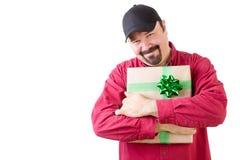 拿着圣诞节礼物的帽子的愉快的人 图库摄影