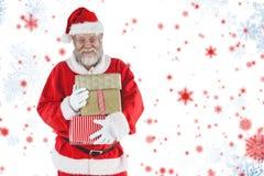 拿着圣诞节礼物的快乐的圣诞老人的综合图象 免版税库存图片