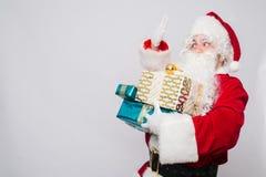 拿着圣诞节礼物的快乐的圣诞老人画象反对白色背景 免版税库存图片