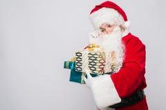 拿着圣诞节礼物的快乐的圣诞老人画象反对白色背景 免版税库存照片