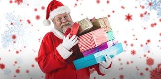 拿着圣诞节礼物的快乐的圣诞老人画象的综合图象 库存照片