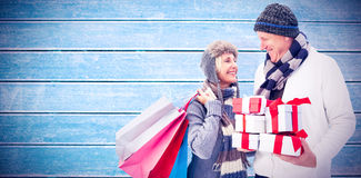 拿着圣诞节礼物的欢乐成熟夫妇的综合图象 免版税库存照片