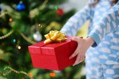 拿着圣诞节礼物的睡衣的孩子由圣诞树 库存图片