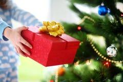拿着圣诞节礼物的睡衣的孩子由圣诞树 免版税图库摄影