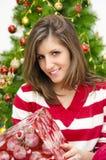 拿着圣诞节礼物的美丽的女孩 免版税库存图片