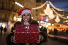 拿着圣诞节礼物的美丽的妇女在晚上 库存照片