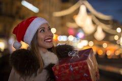 拿着圣诞节礼物的美丽的妇女在晚上 图库摄影